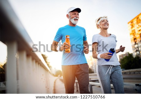 Mature couple jogging and running outdoors in city #1227510766