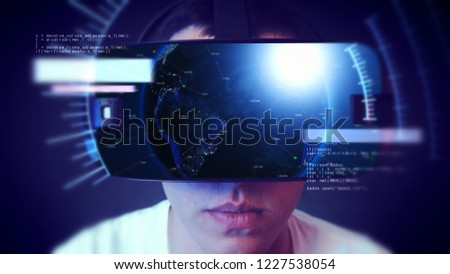 Young man wearing VR headset and experiencing virtual reality. Technology related digital earth network concept. #1227538054