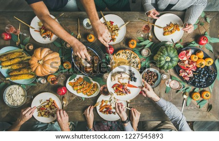 Traditional Thanksgiving or Friendsgiving holiday celebration party. Flat-lay of friends feasting at Thanksgiving Day table with turkey, pumpkin pie, roasted seasonal vegetables and fruit, top view #1227545893