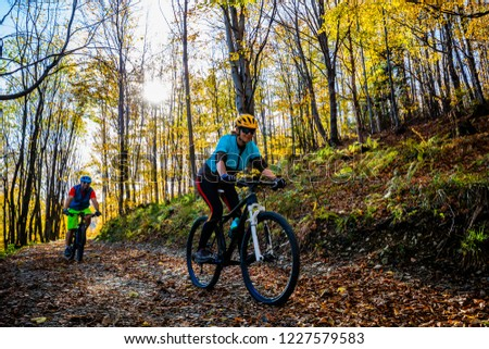 Cycling woman and man at Beskidy mountains autumn forest landscape. Couple riding MTB enduro track. Outdoor sport activity. #1227579583