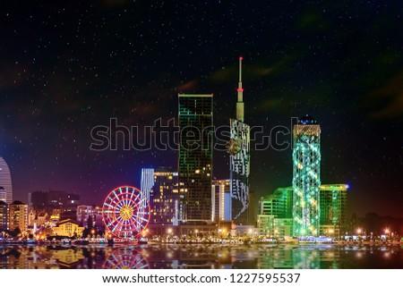 Beautiful night cityscape, view of Batumi city at night. Night reflections of lights in Black Sea port of Batumi, capital of Adjara. Georgia. #1227595537