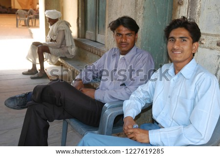 Rajasthan, India - February 25, 2006: Young people sitting at the entrance to Fort Naila with the blurred image of a peasant sitting in the background of the scene #1227619285