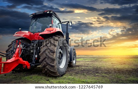 Tractor working on the farm at sunset, a modern agricultural transport, a farmer working in the field, modern tractor closeup #1227645769