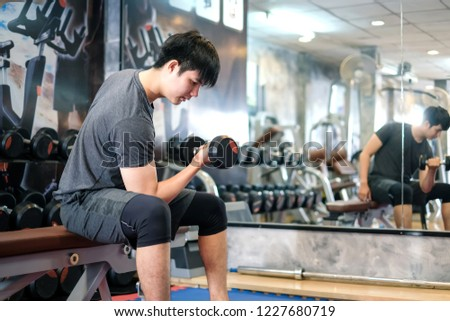 Asian man exercising using dumbbell in the gym. #1227680719
