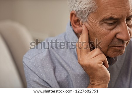 Side view of senior man with symptom of hearing loss. Mature man sitting on couch with fingers near ear suffering pain. Royalty-Free Stock Photo #1227682951