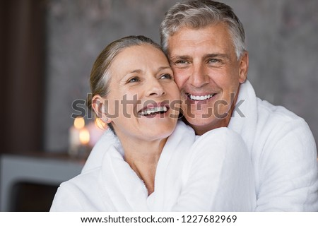Smiling husband embracing cheerful wife from behind at spa. Laughing mature couple enjoying a romantic hug at wellness center after massage. Senior man and woman in white in bathrobe relaxing at spa. #1227682969