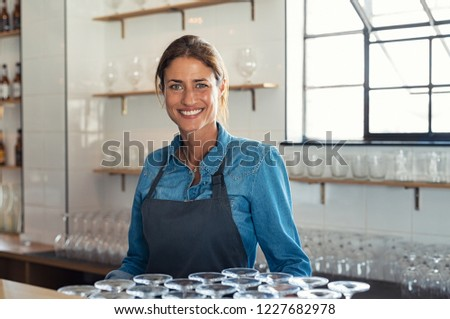 Smiling proud bartender woman standing behind counter and looking at camera. Portrait of beautiful weitress wearing denim shirt with apron. Successful small business owner at pub or coffee shop. #1227682978