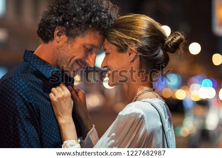 Romantic man and woman on evening date. Happy husband and smiling wife embracing touching head to head on city street at night. Mature couple loving during a romantic night. #1227682987