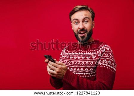 Surprised man in norwegian sweater texting message. Indoor photo of handsome cheerful guy in new year red attire holding phone. #1227841120