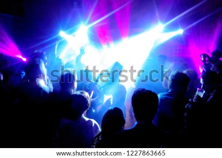 Abstract image of the silhouette of a saxophonist surrounded by a lot of people under the spotlights and neon lights in a pub or disco #1227863665