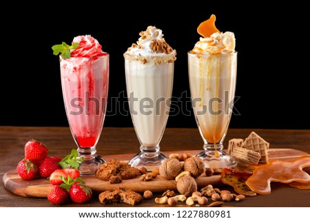 Three sweet milkshakes with nuts, caramel, strawberry and whipped cream at a wooden board on table background. #1227880981