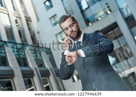 A young businessman with glasses and a beard negotiates a meeting. He has a smartphone in his hands and looks at his watch. #1227946639
