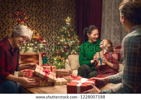Merry Christmas and Happy Holidays! Grandma, mum, dad and child exchanging gifts. Parents and daughter having fun near tree indoors. Loving family with presents in room. #1228007188