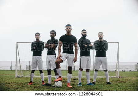 Five football players standing in a formation in front of goalpost. Soccer player standing with one foot on ball with teammates standing behind him with arms crossed. #1228044601