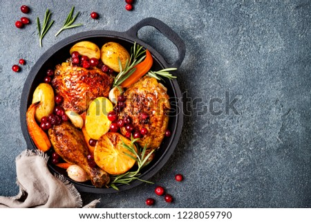 Roasted chicken legs with root vegetables, lemon, garlic, cranberry and rosemary on pan, on black slate stone background #1228059790