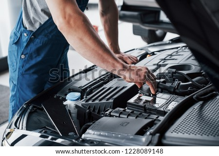 Mechanic hands checking up of serviceability of the car in open hood, close up #1228089148