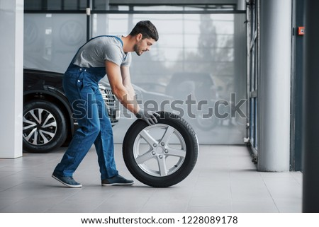 Mechanic holding a tire tire at the repair garage. replacement of winter and summer tires. #1228089178