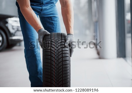 Mechanic holding a tire tire at the repair garage. replacement of winter and summer tires. #1228089196