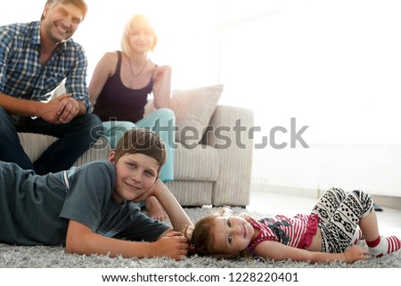 Portrait of children while parents sitting at sofa in living roo #1228220401