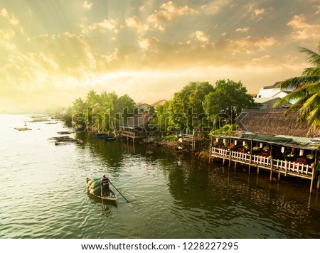 Hoi An traditional fisherman at sunset. Wooden fishing boats on the Thu Bon River in Hoi An Ancient Town (Hoian), Vietnam. Royalty-Free Stock Photo #1228227295