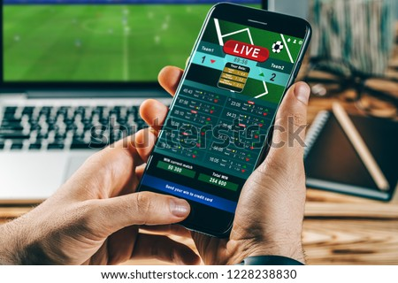 Close up cropped shot of male hands making bets using gambling mobile application on his phone. Man watching football match online broadcast on his laptop waiting for winning results.  #1228238830
