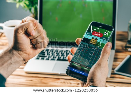Lucky man celebrating victory after making bets using gambling mobile application on his phone. Football match online broadcast on laptop screen on the background. #1228238836