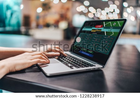 Close up crooped shot of female hands using laptop. Girl sitting in loft coffee shop and making bets online on sport bookmaker's webcite. Royalty-Free Stock Photo #1228238917