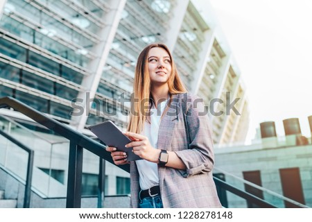 young woman enjoying success after making bets in online bookmaker. Female gambler celebrating victory while watching online broadcast on her mobile device with football stadium on the background. #1228278148