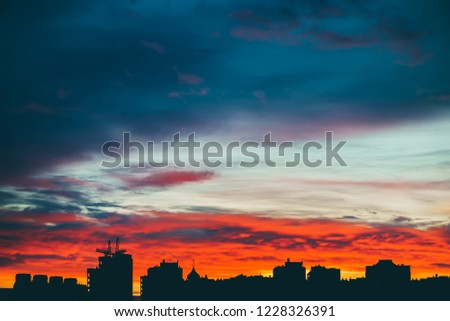 Cityscape with wonderful varicolored vivid dawn. Amazing dramatic multicolored cloudy sky above dark silhouettes of city buildings. Atmospheric background of sunrise in overcast weather. Copy space. #1228326391
