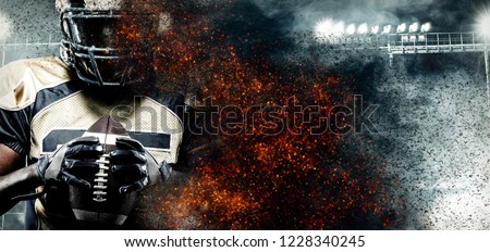 American football player, athlete in helmet on stadium in fire. Sport wallpaper with copyspace on background. #1228340245