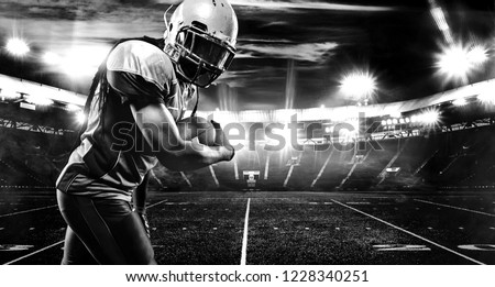 American football player, athlete in helmet with ball on stadium. Black and white photo. Sport wallpaper with copyspace.