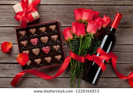 Valentines day with red roses, wine bottle and chocolate box on wooden table. Top view #1228366813