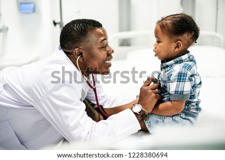 Cheerful pediatrician doing a medical checkup of a young boy #1228380694