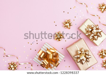 Fashion gifts or presents boxes with golden bows and star confetti on pink pastel background top view. Flat lay composition for birthday, christmas or wedding. #1228398337