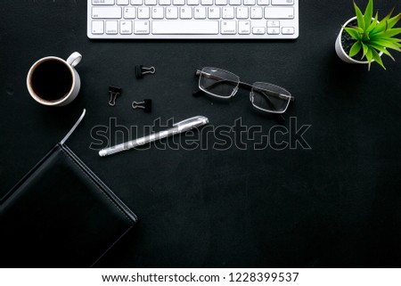 Office desk of chief, director or top manager. Computer keyboard, expensive black notebook, glasses, coffee on black background top view copy space #1228399537
