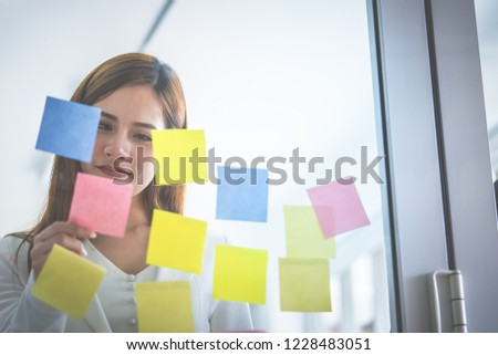 Casual creative business woman is writing ideal and goal on to the windows #1228483051