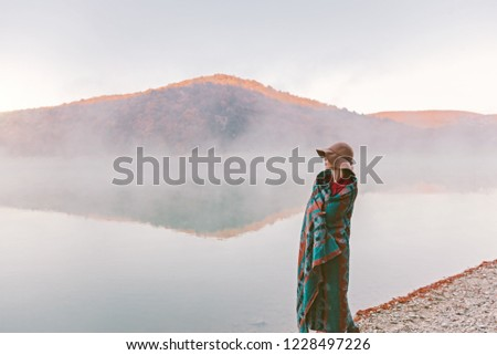 Girl wrapped in warm boho blanket standing and looking at foggy sunrise. Cold morning by the lake. #1228497226