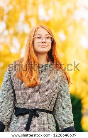 Outdoor close up portrait of beautiful red-haired preteen girl wearing check coat and eyeglasses #1228648639