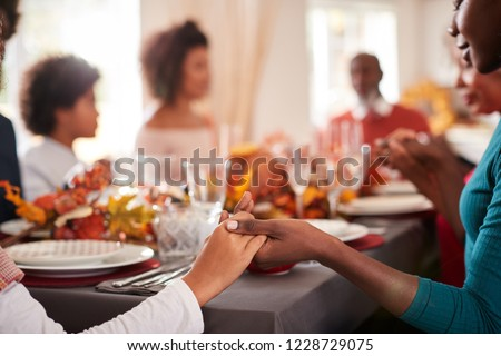 Young black adult woman and her daughter holding hands and saying grace with their multi generation family at the Thanksgiving dinner table, detail, focus on foreground #1228729075