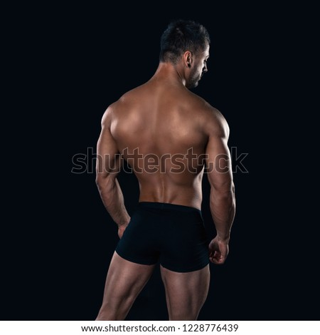 Brutal strong bodybuilder athletic man posing on black background. #1228776439