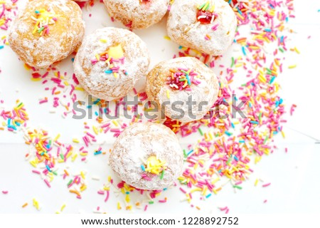 Jewish holiday Hanukka food symbolic, donuts sufganiyot, row of doughnut with assorted flavor jelly inside, decorate with multi pastel color sugar on white isolated background, top view flat lay #1228892752