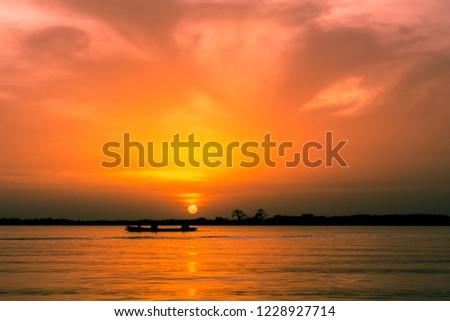 Orange sunset at jungles river with boat, Toubakouta, Senegal #1228927714