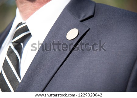 Mens suit Lapel pin closeup of tailored business suit and tie corporate meeting Royalty-Free Stock Photo #1229020042