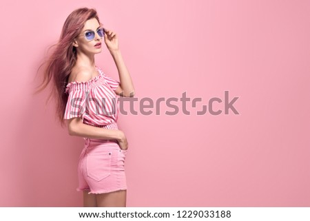 Young Pretty Blonde Girl posing in Studio. Beautiful woman in Stylish romantic Summer Outfit, Trendy Hairstyle, Fashion Sunglasses. Portrait Sexy adorable Lady on Pink vanilla background #1229033188