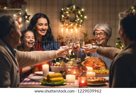Merry Christmas! Happy family are having dinner at home. Celebration holiday and togetherness near tree. #1229039962