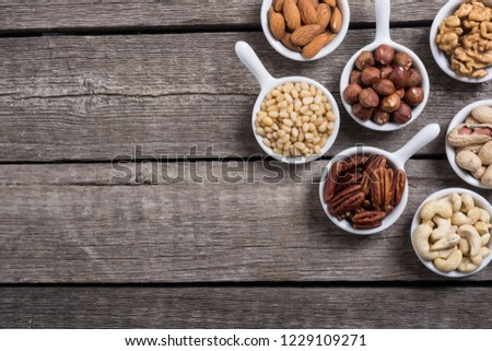 Mix of nuts : Pistachios, almonds , walnuts , pine nut , hazelnuts and cashew . Snack in bowl backgrond #1229109271