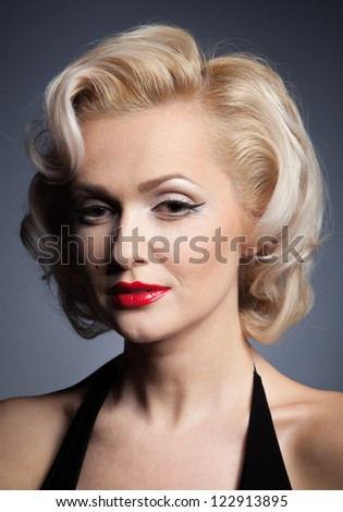 Pretty blond girl model like Marilyn Monroe in black dress with red lips on gray background