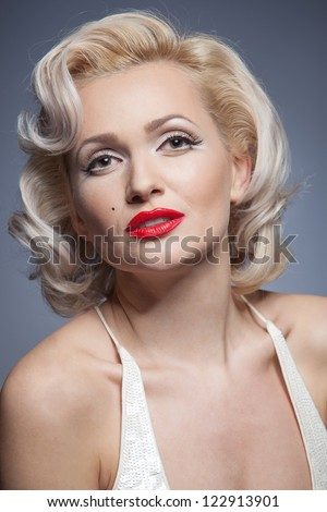 Pretty blond girl model like Marilyn Monroe in white dress with red lips on gray background