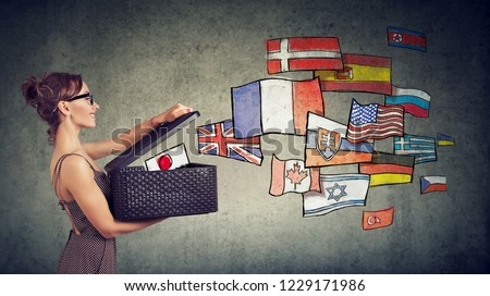 Young woman speaks different languages opening a box with international flags flying away  #1229171986