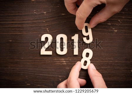 hand changing a wooden number,  symbolizng the change from 2018 to 2019 #1229205679